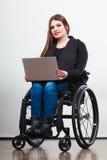 Неработающая женщина с компьтер-книжкой на кресло-коляске Стоковое фото RF