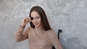 Неработающая молодая женщина прикладывая порошок на ее стороне акции видеоматериалы