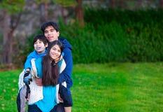 Неработающие biracial автожелезнодорожные перевозки на его сестре, семья катания ребенка стоковые фотографии rf