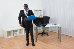 Неработающий бизнесмен стоя в офисе Стоковые Фото