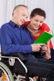 Неработающий и медсестра читая книгу совместно Стоковые Изображения