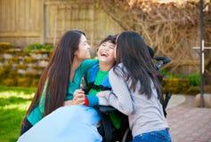 Неработающий мальчик в кресло-коляске смеясь над с предназначенной для подростков сестрой на патио стоковое фото rf
