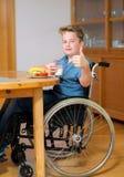 Неработающий мальчик в кресло-коляске с большим пальцем руки вверх стоковые фото