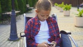 Неработающий подросток в рубашке сидя в кресло-коляске и пользах телефон стоковое фото rf
