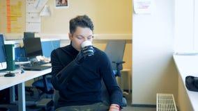 Неработающий человек выпивает воду, используя его искусственную руку Человек с рукой робота