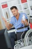 Неработающий человек на кресло-коляске держа кнюппель Стоковая Фотография RF