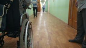 Неработающий человек на кресло-коляске стоя внутренние больница или университет видеоматериал
