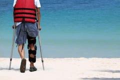 Неработающий человек с костылями пока перемещение на пляже Стоковые Фотографии RF