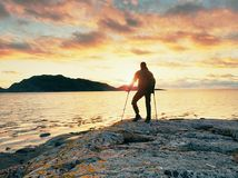 Неработающий человек с протезом и костылями около моря держа руку в воздухе Вечер Солнце Стоковая Фотография