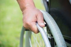Неработающий человек нажимая колесо кресло-коляскы Стоковая Фотография RF