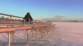Неработающий человек на кресло-коляске медленно управляет через пешеходный мост видеоматериал