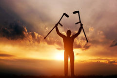 Неработающий человек поднимая его костыли на заходе солнца Медицинские Стоковое Фото