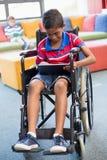 Неработающий школьник на кресло-коляске используя цифровую таблетку в библиотеке Стоковые Фото