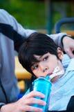 Неработающий biracial мальчик в питьевой воде кресло-коляскы от s стоковые фото