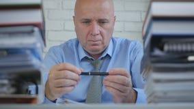 Нервный бизнесмен играя с ручкой и мысль задумчивая стоковое изображение