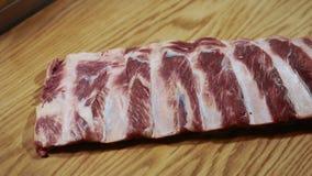 Нервюры говядины кладутся к деревянной разделочной доске на кухню ресторана, концу вверх сток-видео