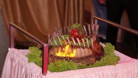 Нервюры свинины сервировки в ресторане с огнем Первоначально сервировка горячих мясных блюд акции видеоматериалы