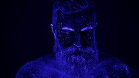 Нереальный танец человека в ультрафиолетовом свете Сильный, мышечный человек стриппер акции видеоматериалы