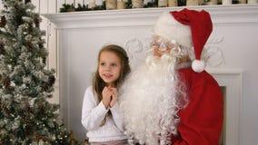 Нерешительная маленькая девочка на подоле Санта Клауса думая о ее настоящем моменте Стоковые Изображения