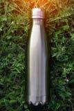 Нержавеющая бутылка с водой thermos, голубой цвет Модель-макет на предпосылке зеленой травы с влиянием солнечного света лоснисто стоковая фотография