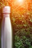Нержавеющая бутылка с водой thermos, голубой цвет Модель-макет на предпосылке зеленой травы с влиянием солнечного света лоснисто стоковое фото