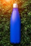 Нержавеющая бутылка с водой thermos, голубой цвет Модель-макет на предпосылке зеленой травы с влиянием солнечного света лоснисто стоковые фотографии rf
