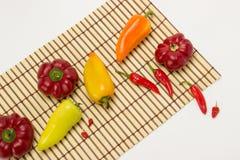 Несколько зрелых сладостных и горячих перцев на салфетке соломы на белизне Стоковые Фото