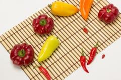 Несколько зрелых сладостных и горячих перцев на салфетке соломы на белизне Стоковые Изображения