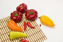 Несколько зрелых сладостных и горячих перцев на салфетке соломы на белизне Стоковая Фотография RF