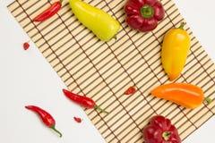 Несколько зрелых сладостных и горячих перцев на салфетке соломы на белизне Стоковое Изображение
