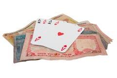 Несколько игральных карт на куче наличных денег стоковое изображение