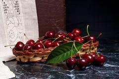 Несколько красных сладостных вишни и больших зеленых лист на таблице Fres Стоковое Фото