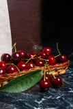 Несколько красных сладостных вишни и больших зеленых лист на таблице Fres Стоковые Изображения