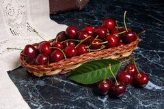 Несколько красных сладостных вишни и больших зеленых лист на таблице Fres Стоковое фото RF