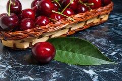 Несколько красных сладостных вишни и больших зеленых лист на таблице Fres Стоковые Изображения RF