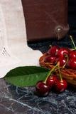 Несколько красных сладостных вишни и больших зеленых лист на таблице Fres Стоковые Фото