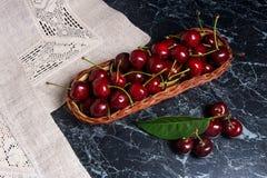 Несколько красных сладостных вишни и больших зеленых лист на таблице Fres Стоковое Изображение RF