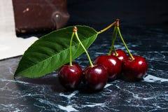 Несколько красных сладостных вишни и больших зеленых лист на темном bac мрамора Стоковые Изображения RF