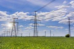 Несколько линий высокого напряжения передачи электроэнергии в зеленом поле Стоковые Изображения