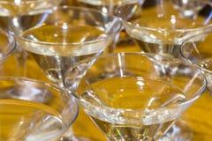 Несколько стекел известного коктеиля Мартини стоят на таблице бара Стоковые Изображения