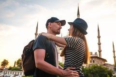 Несколько туристы молодой человек и красивая женщина обнимают против известный во всем мире голубой также вызванной мечети, Стоковое Изображение RF