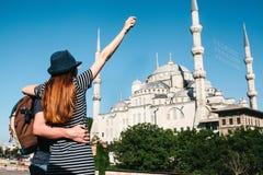 Несколько туристы молодой человек и милая женщина обнимают и смотрят совместно на известный во всем мире голубой мечети внутри Стоковые Изображения