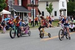 Несколько усмехаясь детей на велосипедах ехать через городок на ежегодном весь парад Oz вещей, Chittenango, Нью-Йорк, 2018 стоковое фото