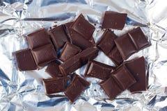 Несколько частей шоколада лож разнообразия сладостно-горькой на серебряной бумаге стоковое фото