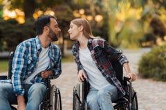 Несколько invalids на кресло-колясках встречали в парке Они нарисованы друг к другу для поцелуя Стоковая Фотография