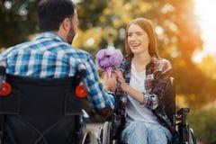 Несколько invalids на кресло-колясках встречали в парке Человек дает букет цветков к женщине Стоковое фото RF