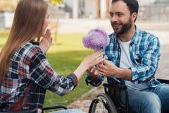 Несколько invalids на кресло-колясках встречали в парке Человек дает букет цветков к женщине Стоковое Изображение