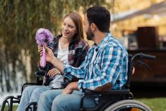 Несколько invalids на кресло-колясках встречали в парке Человек дает букет цветков к женщине Стоковое Изображение RF