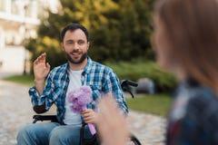 Несколько invalids на кресло-колясках встречали в парке Человек держит букет цветков Стоковые Фото