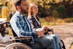 Несколько invalids на кресло-колясках встречали в парке Человек и женщина сидят на береге озера держа руки Стоковая Фотография RF